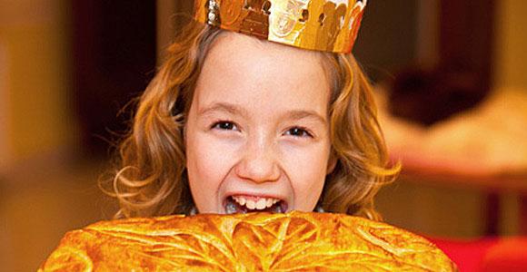 sourire d'enfant au dessus d'une galette des rois.