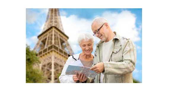 couple de seniors regardant un plan au pied de la tour Eiffel