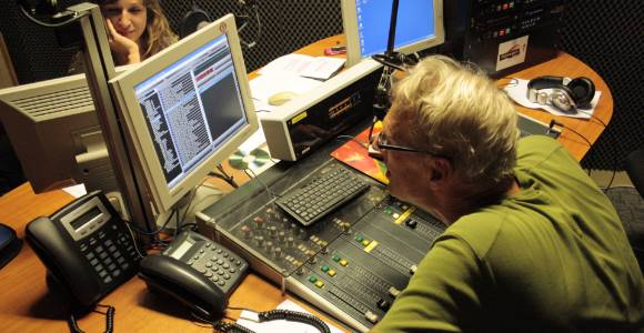 Animateur radio derriere une console.