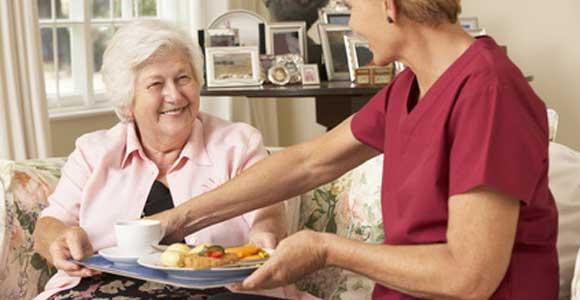 Femme apportant un plateau repas à une autre femme plus agée.